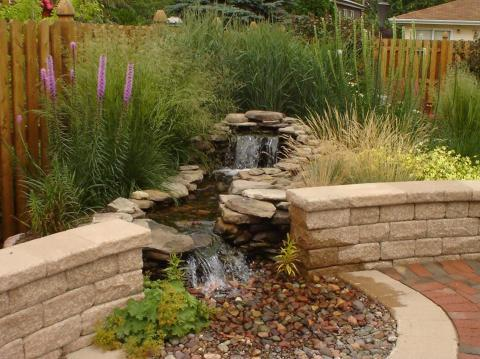 Traditional Landscape with short stone wall around patio