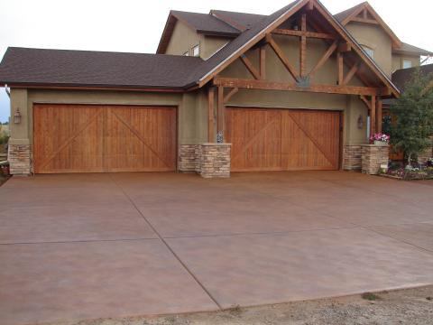 Traditional Driveway with dark stained wood garage doors