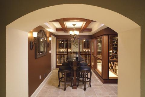 Mediterranean Wine Cellar with elegant wood framed wall mount mirror with crown detail