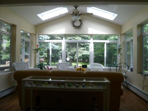 Transitional Sunroom with black metal side table and chair