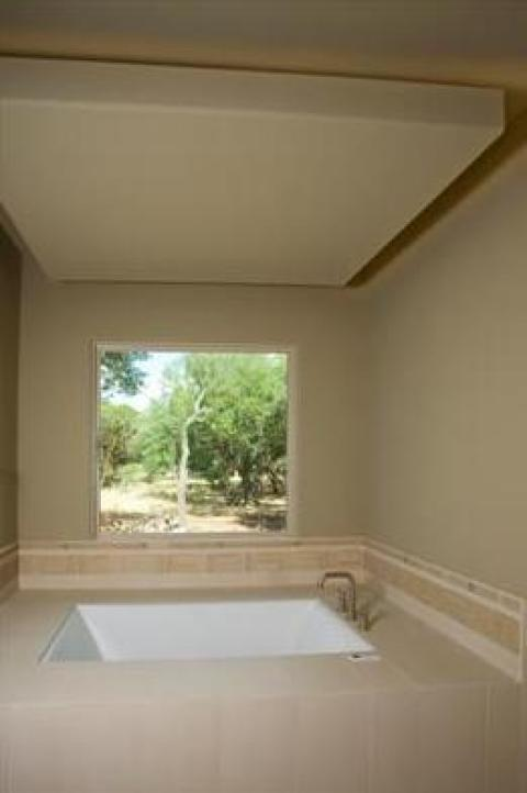 Transitional Master Bathroom with large window over tub