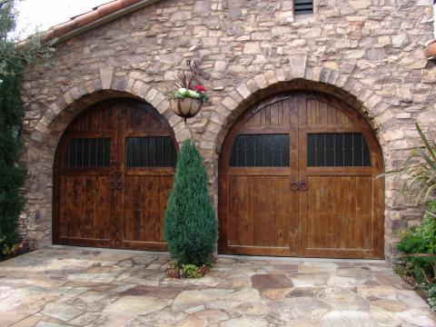 Mediterranean Garage with dark rustic wood garage doors