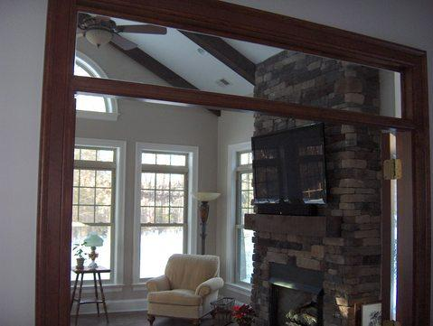 Transitional Sunroom with stone stacked fireplace surround