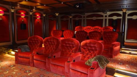 Eclectic Home Theater with red velvet theater seats