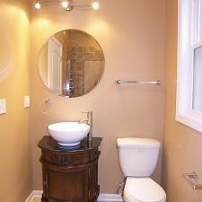 Traditional Powder Room with dark wood elegant vanity cabinet
