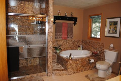 Eclectic Master Bathroom with gold granite shower surround