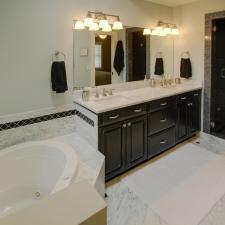 Traditional Master Bathroom with white marble tile flooring with black accent tile