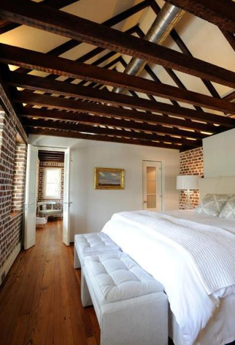 Eclectic Bedroom with dark wood ceiling beams