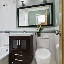 Contemporary Bathroom with dark brown bathroom vanity with white porcelain counter top