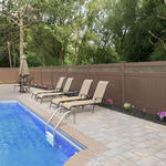 Traditional Pool with brown vinyl fencing with lattice panel