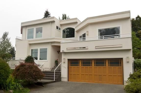 Contemporary home exterior with beige stucco siding for Tuck under garage