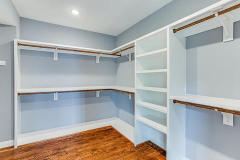 Transitional Closet with stained oak wood floor