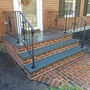 Colonial Revival Porch with black wrought iron railing