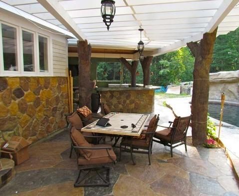Eclectic Patio with tree trunk pergola supports