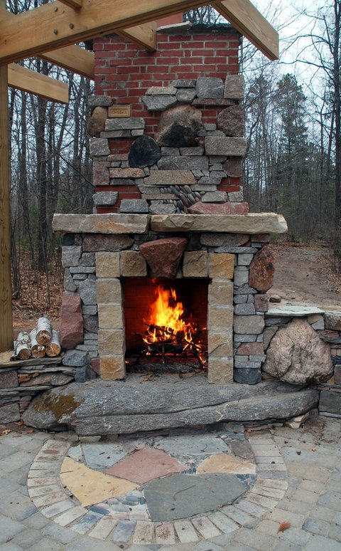 Eclectic Patio with stone slab fireplace base