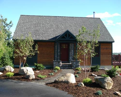 Cottage home exterior in providence asphalt driveway for River rock columns