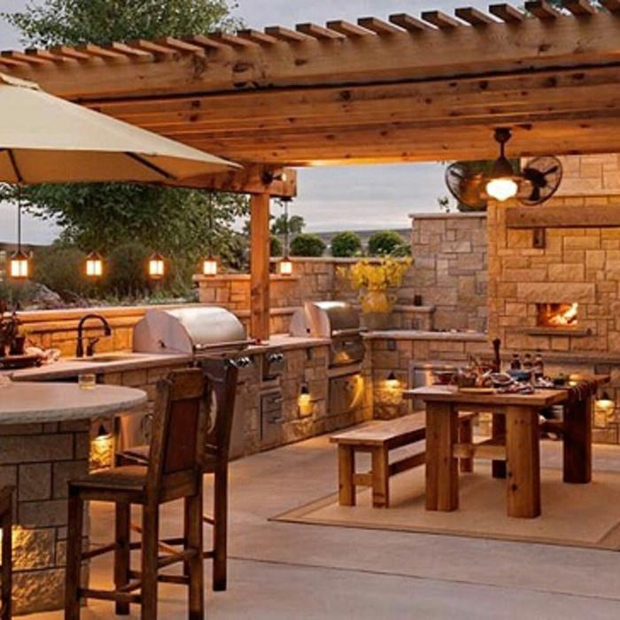 Outdoor kitchen with fireplace and dining table