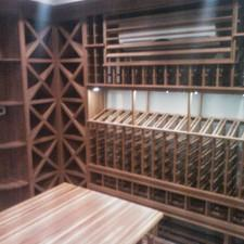 Contemporary Wine Cellar with wood top table with wine rack below