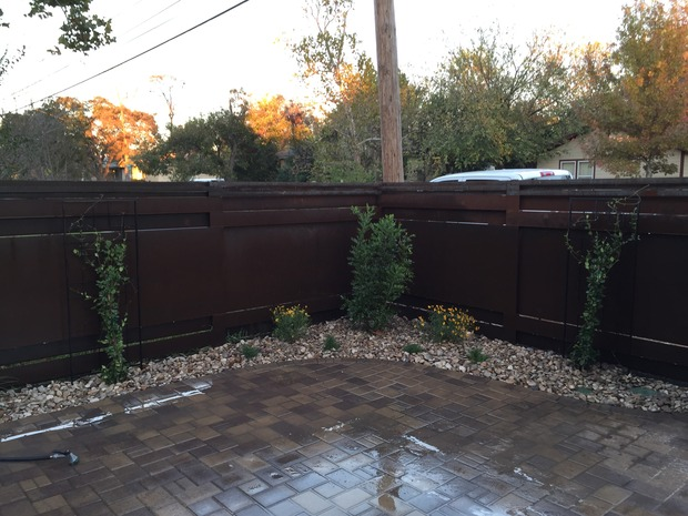 Rustic patio in austin brown finish stone lined beds for Home turf texas landscape design llc