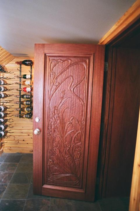 Eclectic Wine Cellar with hand carved wood door